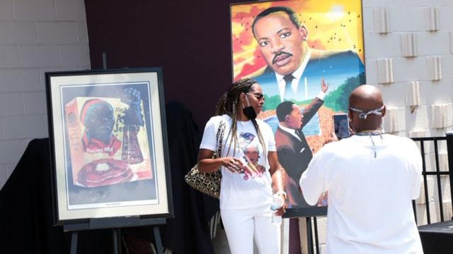 A guest poses for a photo in front of art work depicting Martin Luther King Jr. during a Juneteenth celebration at the King Arts Complex.