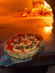 Neapolitan style pizza is distinct for its crispy, slightly charred crust that comes from being cooked at very high temperatures in a wood-fired pizza oven.