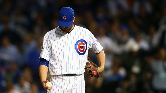 Chicago Cubs relief pitcher Justin Grimm (52) reacts after giving up a run in the seventh inning against the New York Mets in game three of the NLCS at Wrigley Field.