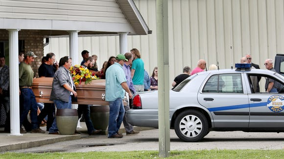 Pallbearers carry the casket with Gary Rhoden, 38, who was one of the seven family members, plus a fianceŽ, killed last week in Pike County.