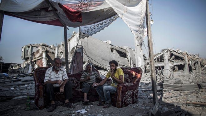 Palestinians sip tea and smoke cigarettes on a salvaged sofa outside their destroyed home in the Shujaiya neighbourhood, east Gaza City, on Wednesday. Israel pulled its last soldiers out of the Gaza Strip on Tuesday after four weeks of fighting, as a temporary truce went into effect aimed at giving the sides three days to negotiate a longer-term deal.