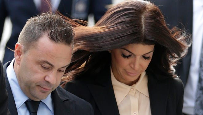 'The Real Housewives of New Jersey' stars Giuseppe 'Joe' Giudice, 43, left, and his wife, Teresa Giudice, 41, of Montville Township, walk toward Martin Luther King, Jr. Courthouse before a court appearance, Thursday, Oct. 2, 2014, in Newark, N.J. The Giudices are scheduled to be sentenced on federal conspiracy and bankruptcy fraud charges. (AP Photo/Julio Cortez)