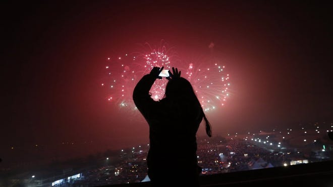 A woman uses her smartphone to take picture of fireworks while celebrating the New Year at the Imjingak Pavilion near the border village of Panmunjom in Paju, South Korea, Friday, Jan. 1, 2016.