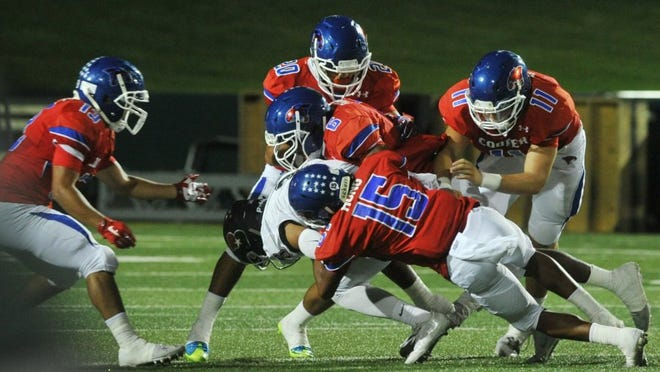 Nellie Doneva/Reporter-News Cooper defense tackles a Bowie ball carrier Friday.