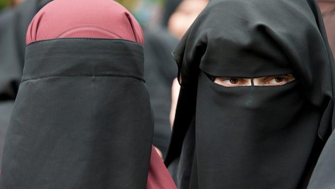 In this June 28, 2014 file photo veiled women attend a speech by preacher Pierre Vogel, in Offenbach, near Frankfurt, Germany.