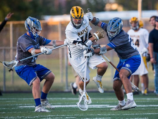 Naples' Christian Druin jumps through a double team during the District 20 high school boys lacrosse championship at Barron Collier High School on Thursday, April 19, 2018.