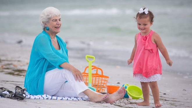 Nancy Schlossberg plays on the beach at Longboat Key, Fla.,  with her granddaughter Stevie, 2 1/2. Schlossberg is trying to figure out how to pay for her three grandchildren's college educations.