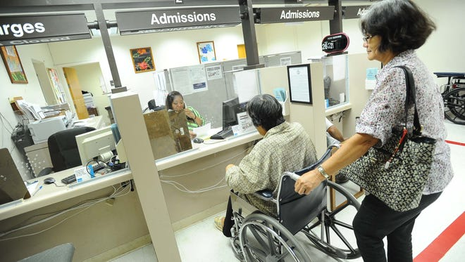 Flor Paule, right, pushes Tamuning resident Leonarda Torres' wheelchair to the admissions counter at Guam Memorial Hospital in September 2013.
