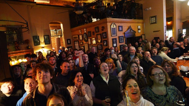 """Attendees at a """"Jeopardy!"""" viewing party celebrate as Broadwater teacher Eric Hack responds correctly to a clue during the show Feb. 4 in Cape Charles. Hack won the round and will advance in the show's Teachers Tournament."""