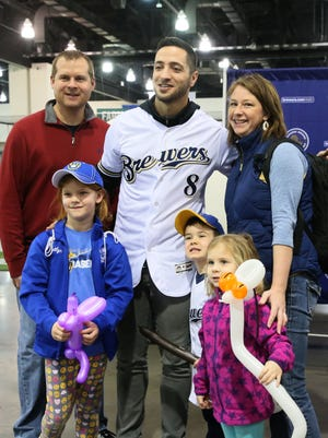 Ryan Grunewald, his wife Leah and their children Kaitlyn, 7 (lower left), Emma, 4 (lower right), and nephew Luke Meseck, 4 (center), have their photo taken with Ryan Braun.