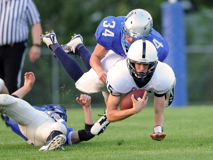 WLA Sophmore Dillon Jerdee (34) tackles Lakeside Lutheran's Nick Chesterman (15) Friday night during a game at Winnebago Lutheran Academy.  Friday August 22, 2014. Doug Raflik/Action Reporter Media