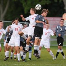 Jumping in unison to get to the ball first are Canton's Nick Wendel (No. 4) and Plymouth's Calvin McCracken (No. 16).