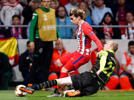 Sporting's Jeremy Mathieu tackles Atletico's Antoine Griezmann during the Europa League quarterfinal first leg soccer match between Atletico Madrid and Sporting CP at the Metropolitano stadium in Madrid, Thursday, April 5, 2018. (AP Photo/Francisco Seco)