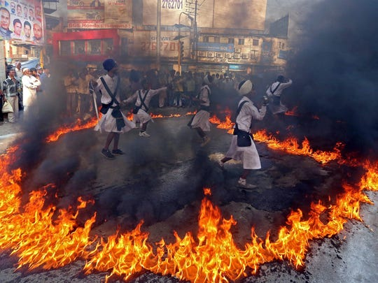 Sikh devotees perform martial arts in a fire ring during