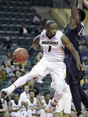 Missouri's Terrence Phillips (1) paases the ball around Xavier's Malcolm Bernard during the second half of the Tire Pros Invitational NCAA college basketball tournament, Thursday, Nov. 17, 2016, in Kissimmee, Fla. Xavier won in overtime 83-82. (AP Photo/John Raoux)
