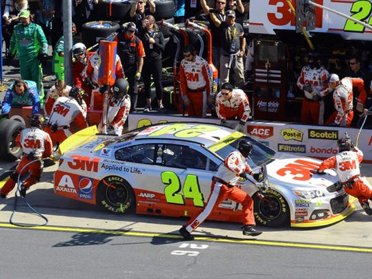Crew members perform a pit stop on Jeff Gordon's car during the NASCAR Sprint Cup series auto race at Charlotte Motor Speedway in Concord, N.C., Sunday, Oct. 11, 2015. (AP Photo/David Graham)