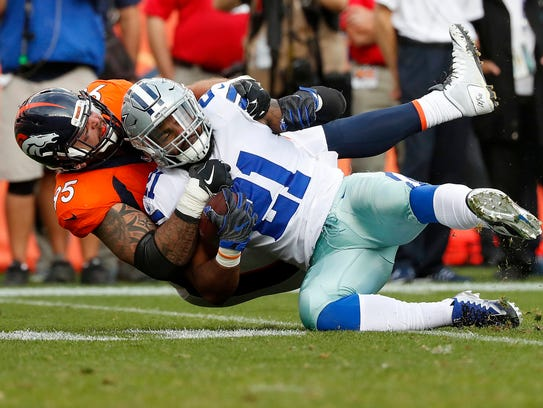 Cowboys running back Ezekiel Elliott is tackled against the Broncos on Sept. 17.