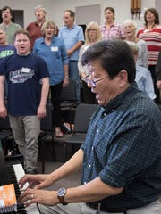 Artistic Director Xiaolun Chen plays the piano as he