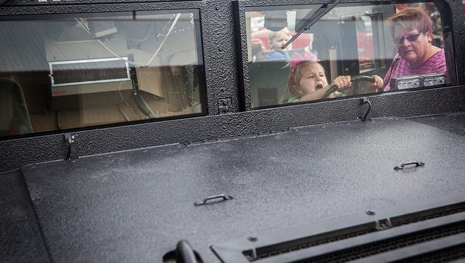Threya Orebaugh fights crime in a Muncie SWAT armored vehicle during the Prevent Child Abuse event at the Delaware County Fairgrounds Saturday, Oct. 24, 2015.