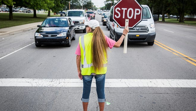 A crossing guard works outside of Northside Middle School on Bethel Avenue Wednesday afternoon.