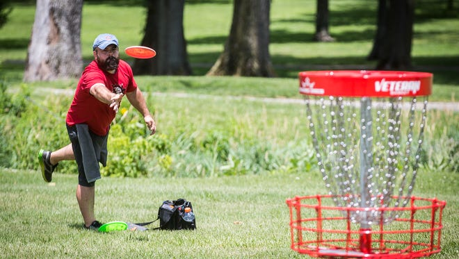 Jordan Jones and Justin Jones compete in a round of disc golf at Goodrich Park in Winchester Saturday afternoon.
