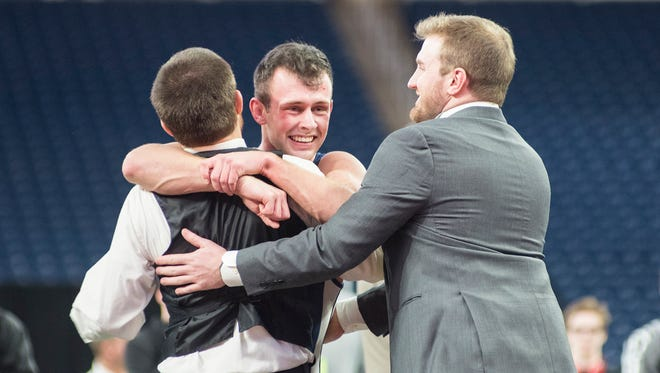 Richmond High School's Alex Roberts, center, celebrates with his coaches after defeating Lake Fenton's Sean Trombley 5-3 in the MHSAA Division 3 Wrestling Championships at Ford Field March 3.