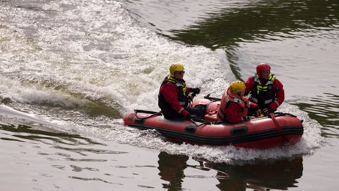 Indianapolis Fire Department's Swift Water Rescue Team 14 prepares to go in the water to investigate a body in the White River, near Michigan Road on Wednesday, May 16, 2018.