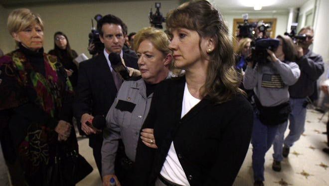 In this March 2009 photo, Cheryl McCafferty is escorted out of Campbell Circuit Court after a jury found her guilty of manslaughter in the first degree for killing her husband in June 2007.