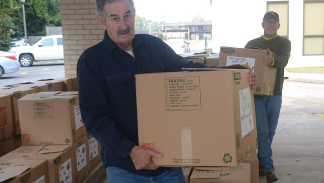 Ray Vercher (left) and Lane Howe, both Calvary Baptist Church members and volunteers with the church's Mission CenLa program, load Thanksgiving boxes into waiting cars Saturday.