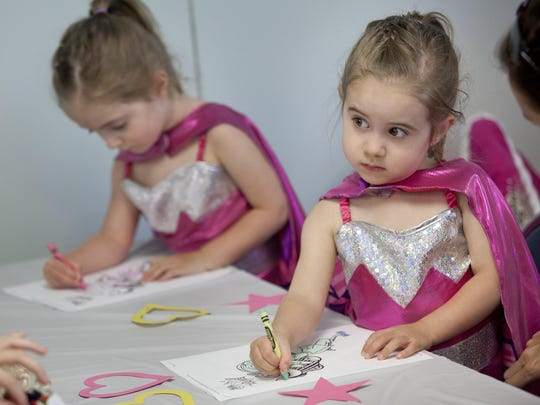 Ella Magneson, 3, of Port Huron, is dressed as a super hero as she colors along with her twin sister Kate Magneson, 3, during a Barbie-themed party at the library.