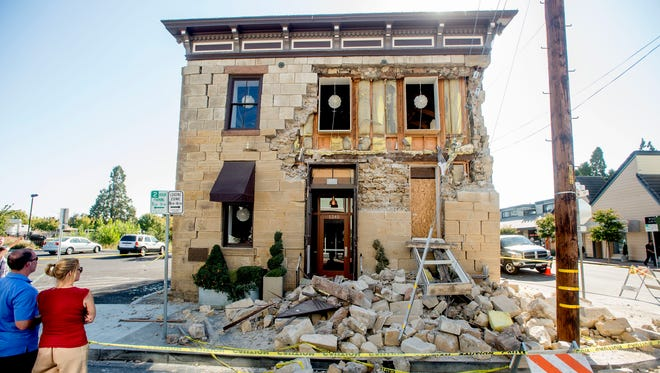 An Aug. 24 photo shows pedestrians examining a crumbling facade following an earthquake at the Vintner's Collective tasting room in Napa, Calif.