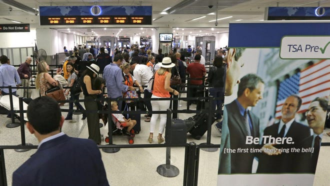 Travelers stand in line May 26 as they prepare to pass through a Transportation Security Administration checkpoint at Miami International Airport.