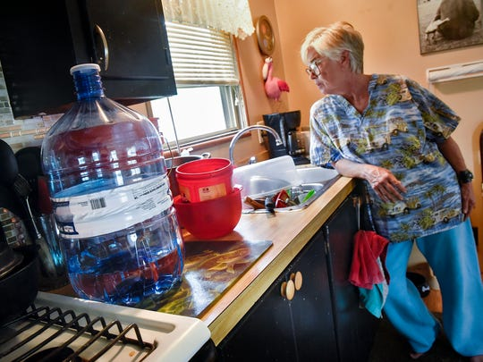 Barbara Durham stands in her kitchen next to a bottle of water and the containers she is using to wash dishes in her home Monday, June 25, in Sartell. Durham is a resident of Sartell Mobile Home Park, where some residents have been without water since Thursday due to a water line break.