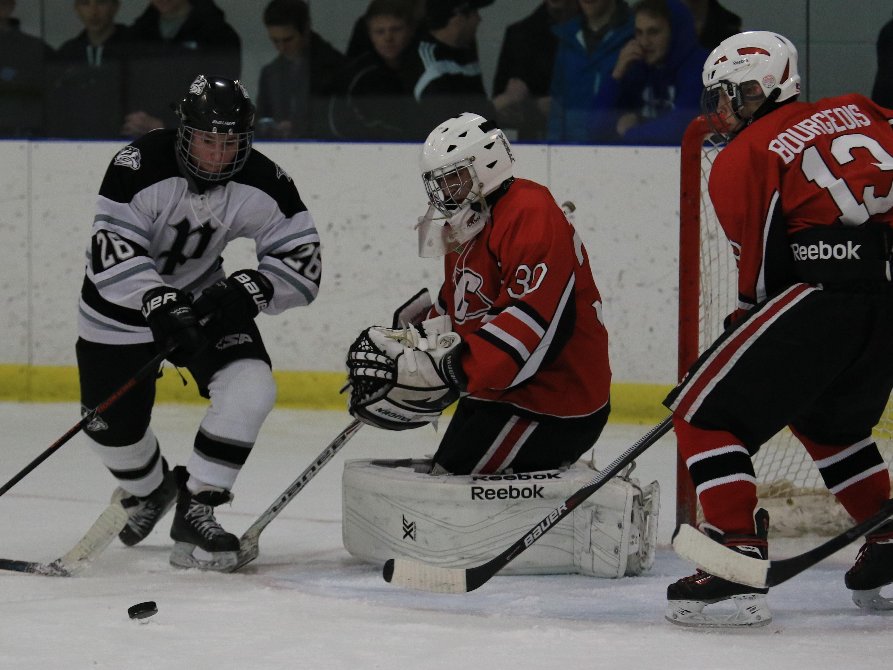 Plymouth's Josh Weber (No. 26) chases the puck in front of Canton goalie Isaac Salinas. At right for the Chiefs is Daniel Bourgeois.