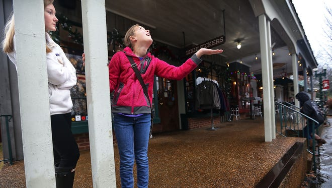 Ellie Schubert, catches raindrops outside of Dixie Pickers in the Collierville Town Square as she waits with her sister, Abigail Schubert, for their parents.