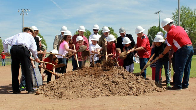 Flippin School District board members, superintendent, contractors and students break ground Friday for a new elementary school slated to be completed by August 2016.