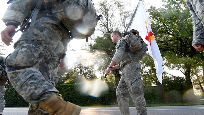 First class cadet Andrew Skibicki with the Virginia Military Institute carries a VMI flag. He marches with about 20 other cadets as they follow North Augusta Street through Staunton after resuming their 80-mile trek to New Market battlefield Friday morning, Sept 4, 2015.