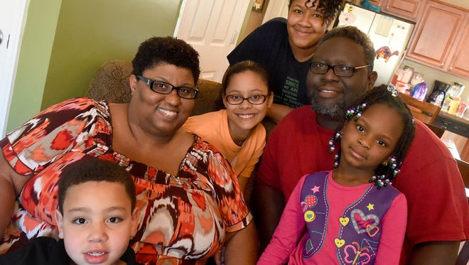 Sonya and Jonathan Payne are photographed with grandson Isiaha Evans (bottom left), 7, and adopted daughters Ariel Payne (center), 16; Tai Payne (top), 15; and JaNya Payne (bottom right), 5, in their home in Staunton on Friday, Nov. 19, 2015. Sonya and Jonathan have fostered over 40 children.