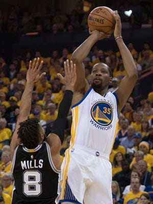Golden State Warriors forward Kevin Durant shoots the basketball against San Antonio Spurs guard Patty Mills during the second quarter in Game 1 of the Western Conference finals.
