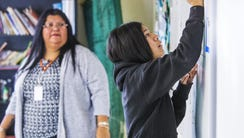 Teacher Barbara Parsons, left, watches Marisol Soke,
