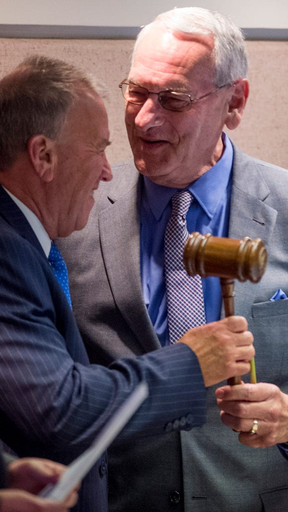 Speaker of the House Mac McCutcheon, center, is handed the gavel by acting Speaker Rep. Victor Gaston after McCutcheon was elected Speaker of The House during the first day of the special session of the Alabama Legislature held at the Alabama Statehouse in Montgomery, Ala., on Monday August 15, 2016.