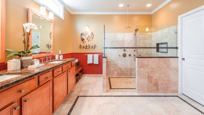 In a curbless design, the shower floor is flush and continuous with the bathroom floor. Gravity and the slope of the floor prevents water from spilling out into the bathroom.