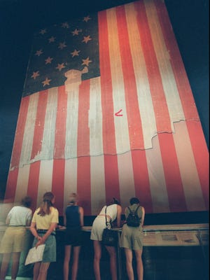 """Members of the public look at the American flag, the """"Star-Spangled Banner"""" at the Smithsonian Museum of American History in Washington in 1997. This is the flag that Francis Scott Key saw flying """"in the dawn's early light"""" on Sept. 14, 1814, over Fort McHenry in Baltimore."""