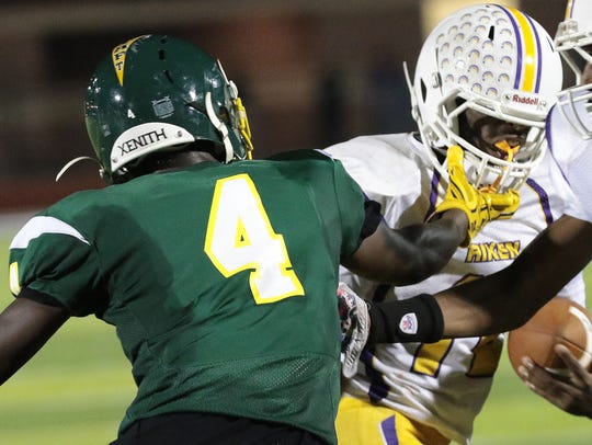 Aiken's Tim Williams (10) tries to run away from Taft's