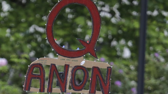 """In this May 14, 2020, photo, a person carries a sign supporting QAnon at a protest rally in Olympia, Wash., against Gov. Jay Inslee and Washington state stay-at-home orders made in efforts to prevent the spread of the coronavirus. QAnon is a wide-ranging conspiracy fiction spread largely through the internet, centered on the baseless belief that President Donald Trump is waging a secret campaign against enemies in the """"deep state"""" and a child sex trafficking ring run by satanic pedophiles and cannibals. It is based on cryptic postings by the anonymous """"Q,"""" purportedly a government insider."""