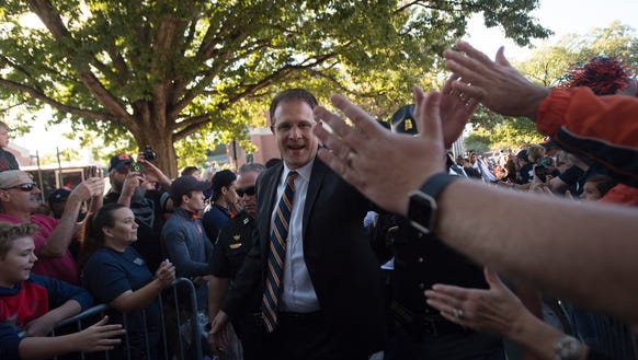 Auburn head coach Gus Malzahn high five fans during