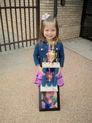 Elliana Nelson, 6, poses with her trophy and her photo