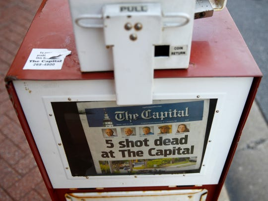 A Capital Gazette newspaper rack displays the day's