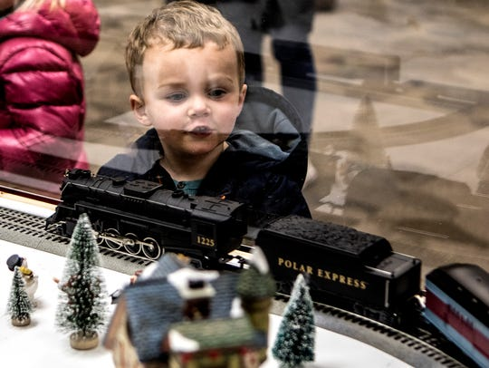 Max Hoben, 3, looks through the glass as model trains