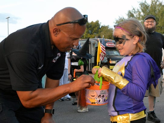 Las Cruces Fireman Harold Caldwell gives Aerynn Viruet, 6, a treat as her father watches in the background during the inaugural HalloweenFest and Family Wellness Fair on Monday, Oct. 31, 2016, at the Doña Ana County Government Center parking lot.